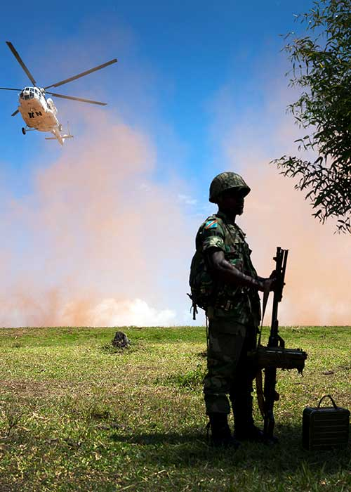 Soldier stands waiting while UN helicopter is landing