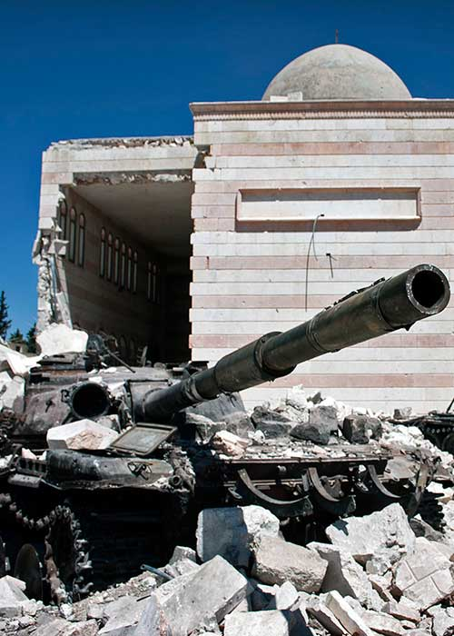 Abandoned tank standing in front of ruined mosque