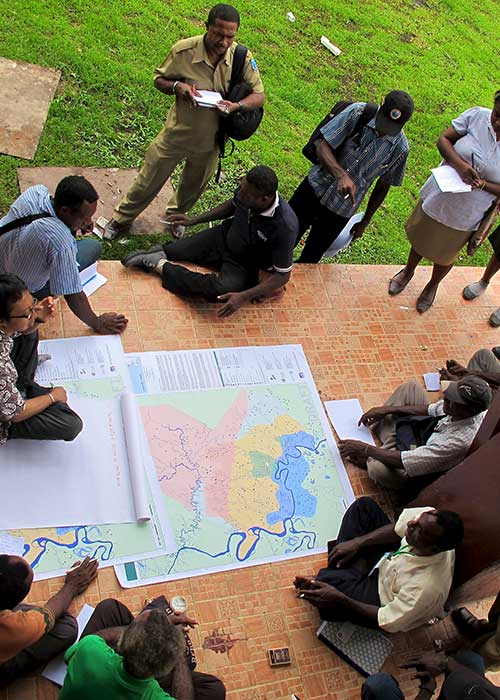 Group of humanitarian workers discussing around a map
