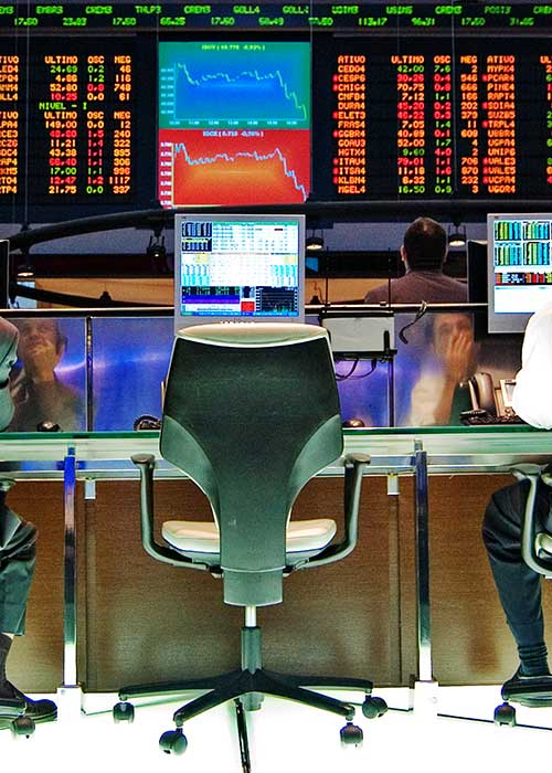Two stock market traders reflected in their screens, sitting in front of list of stock prices