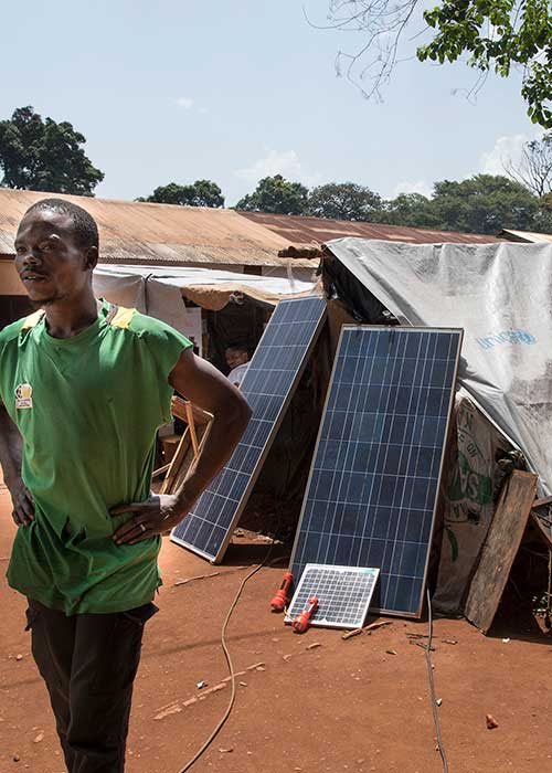 Man standing outside tent with solar panels in IDP camp Site du Petit Seminaire St.Pierre Claver in Bangassou, Central African Republic.