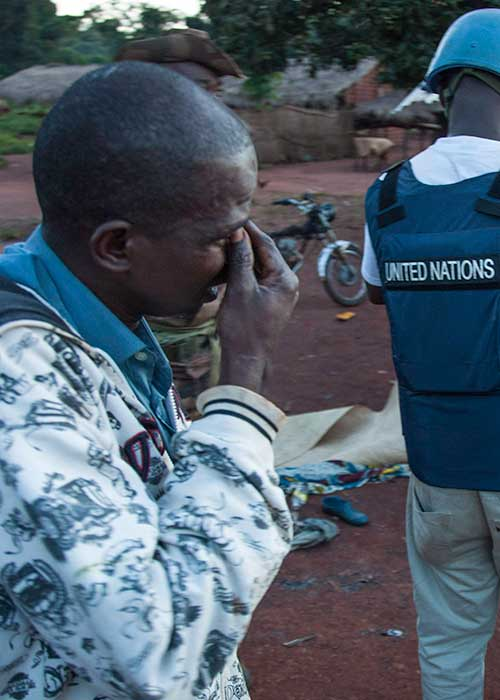 Crying young man behind a UN peacekeeper following an incident