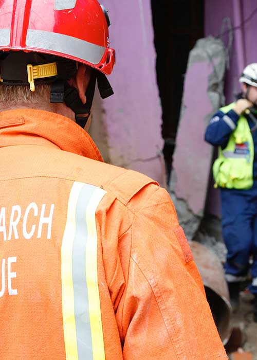 Search and rescue workers by a destroyed building