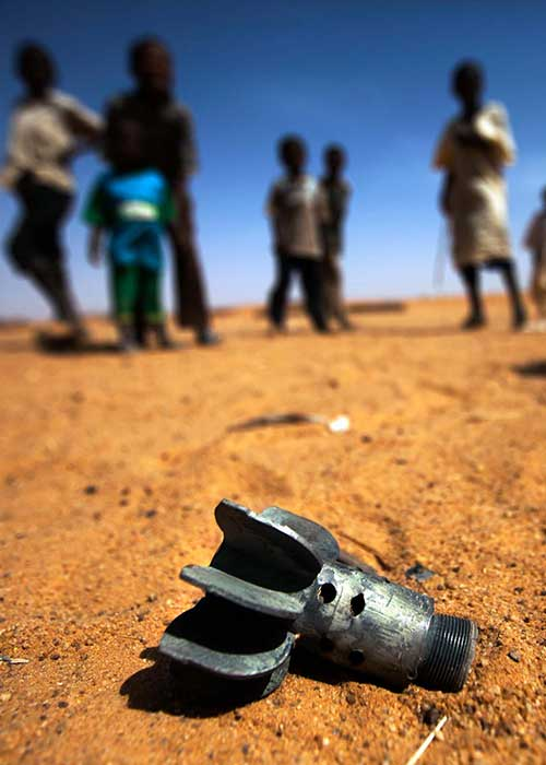 Remnant of a mortar projectile on the ground in front of a group of children in an IDP camp