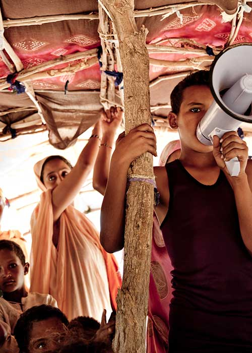 Refugee children in a tent using a megaphone