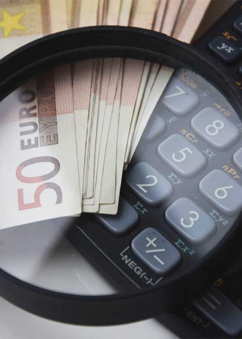 Magnifying glass over euro bills and a calculator