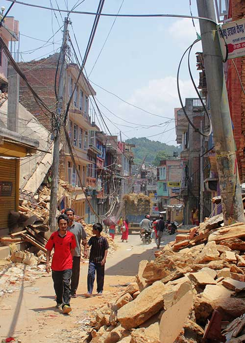 People walking down street in urban environment where several buildings have collapsed following a disaster