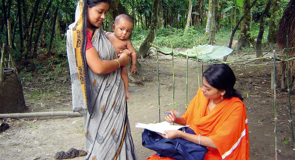 A female interviewer talking to a mother in rural Bangladesh