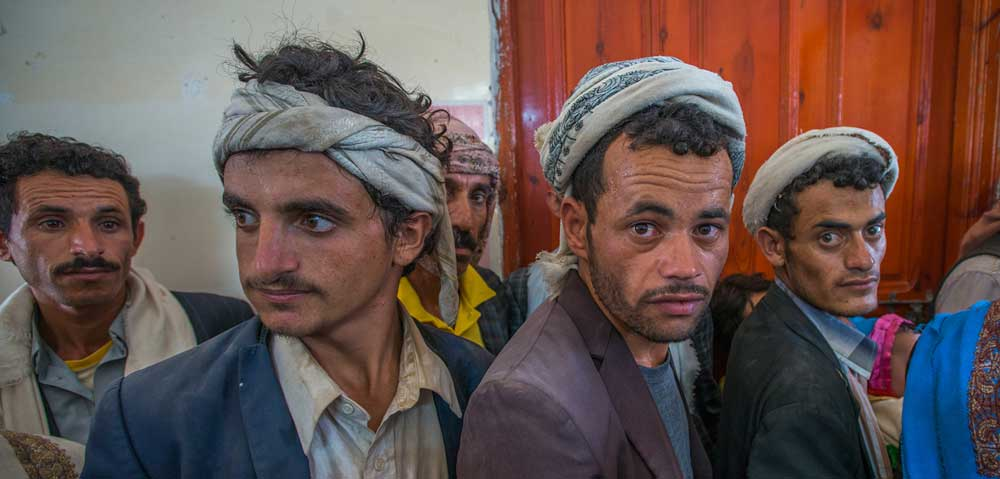 Yemeni fathers line up at a remote EU-supported clinic where they have brought their children.