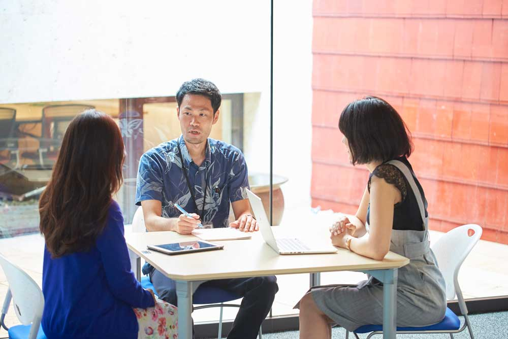 Three people discussing around a table
